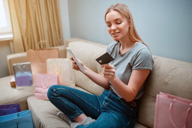 Молодой счастливый покупатель с кредитной картой и планшетом покупает в интернет-магазине, сидя на диване с сумками