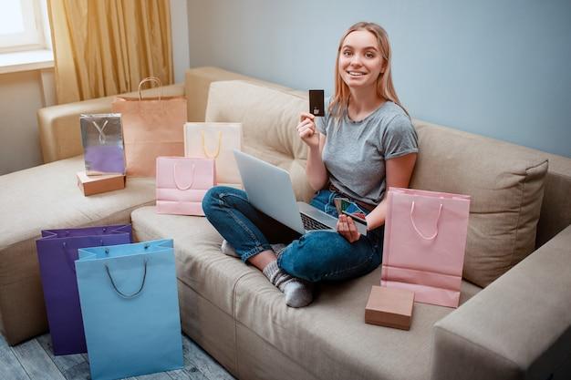 쇼핑백과 함께 소파에 앉아있는 동안 신용 카드로 젊은 행복 쇼핑객은 최고의 판매를 선택하고 있습니다
