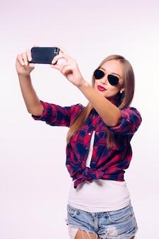若い幸せな笑顔の女の子は白い壁に自分撮りを取ります