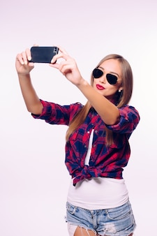 Young happy smile girl take selfie on white wall