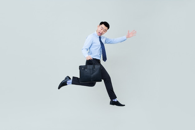 Young happy smiling asian  professional man  jumping in midair