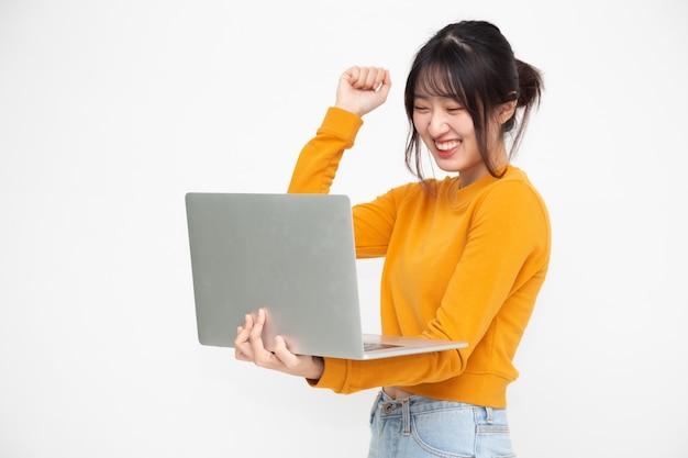 Молодая счастливая усмехаясь азиатская женщина в желтой вскользь одеждах держа компьтер-книжку с беседовать и смеяться над