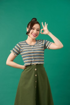 Young happy smiling beautiful woman in casual clothing, showing okay gesture