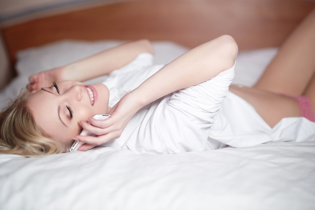 Young happy smiling beautiful woman lying on bed and speaking on phone