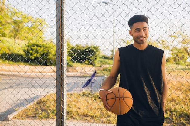 Молодой счастливый улыбающийся темнокожий мужчина занимается спортом, играет в баскетбол на восходе солнца, активный образ жизни, летнее утро