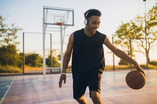 Молодой счастливый улыбающийся темнокожий мужчина занимается спортом, играет в баскетбол на рассвете, слушает музыку в наушниках, активный образ жизни, летнее утро