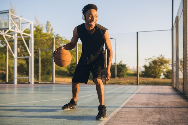 Young happy smiling black man doing sports, playing basketball on sunrise, listening to music on headphones, active lifestyle, summer morning