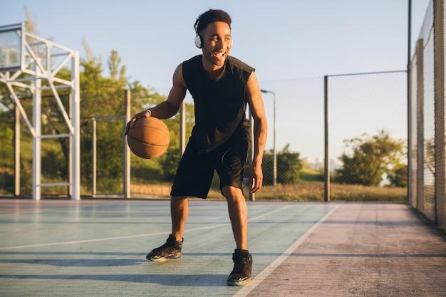 Giovane uomo di colore sorridente felice che fa sport, gioca a basket all'alba, ascolta la musica in cuffia, stile di vita attivo, mattina d'estate
