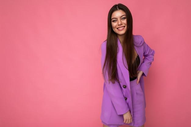 Молодая счастливая улыбающаяся брюнетка женщина красивый привлекательный очаровательный элегантный модный стильный костюм с пиджаком, изолированным на розовом фоне с копией пространства.