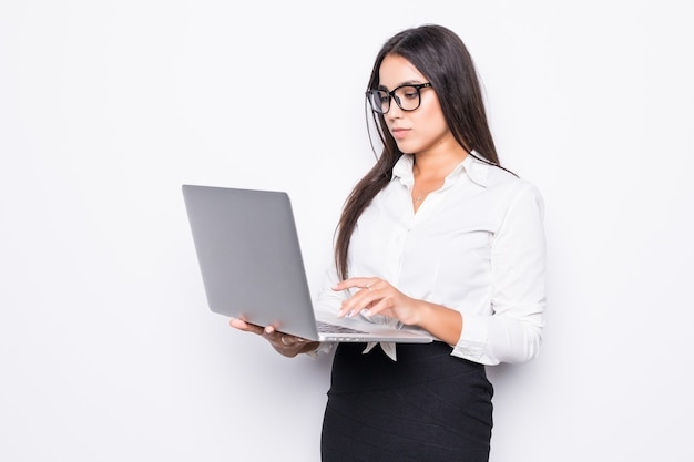 Young happy smiling business woman in casual clothes holding laptop and sending email isolated on white