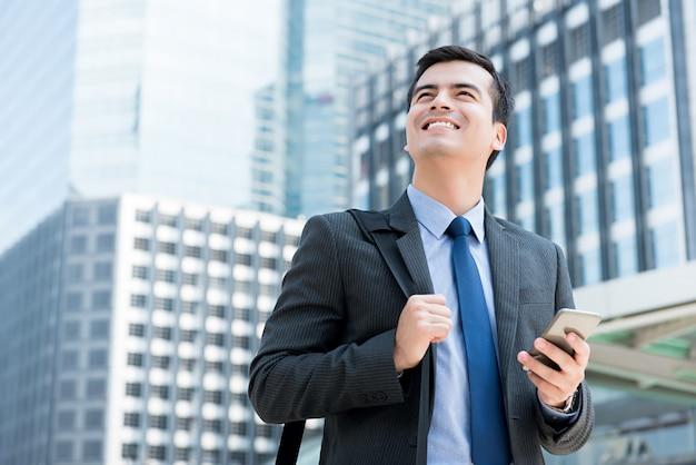 Молодой счастливый улыбающийся бизнесмен, глядя вверх, держа мобильный телефон и сумка для переноски в городе