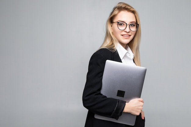 Young happy smiling businesswoman holding laptop isolated