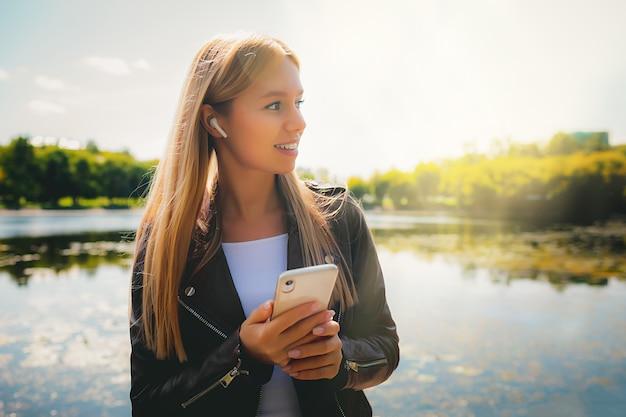 タブレットと携帯電話で公園を歩く若い幸せな笑顔の白人の成功大人の女の子