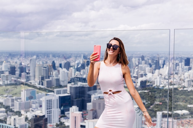 Young happy smiling caucasian woman traveller in fitting dress and sunglasses on high floor in bangkok holding phone