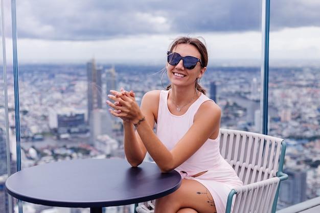 Viaggiatore di giovane donna caucasica sorridente felice in abito di montaggio e occhiali da sole al piano alto a bangkok elegante donna che esplora incredibile vista sulla grande città