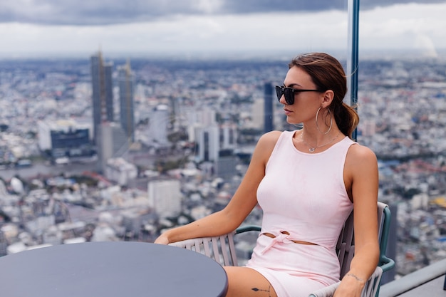 Young happy smiling caucasian woman traveller in fitting dress and sunglasses on high floor in bangkok stylish female exploring amazing big city view
