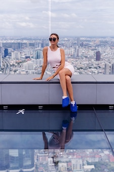 Young happy smiling caucasian woman traveller in fitting dress and sunglasses on high floor in bangkok
