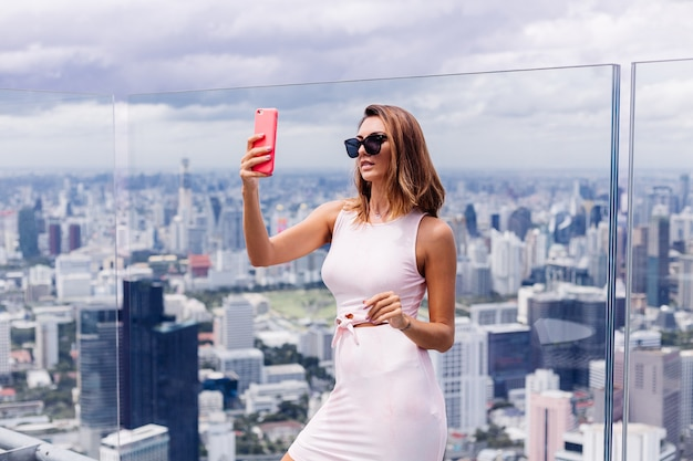 Молодая счастливая улыбающаяся кавказская женщина-путешественница в подходящем платье и солнцезащитных очках на высоком этаже в бангкоке, держащая телефон