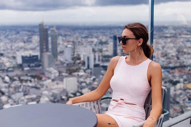 Молодая счастливая улыбающаяся кавказская женщина-путешественница в подходящем платье и солнцезащитных очках на высоком этаже в бангкоке. стильная женщина изучает удивительный вид на большой город.