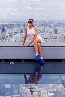 バンコクの高層階にドレスとサングラスを合わせて若い幸せな笑顔の白人女性旅行者