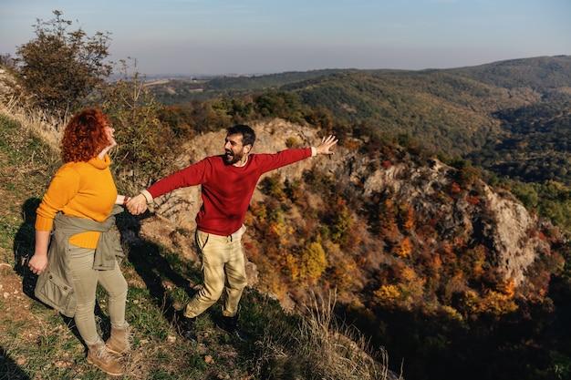 Молодые счастливые улыбающиеся пара в любви, проводить выходные на природе. пара, взявшись за руки и наслаждаясь красивой природой в солнечный осенний день.