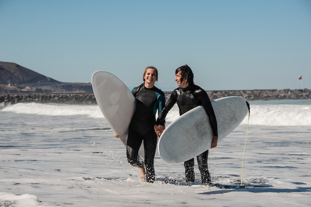 Young and happy smiling couple of surfers in black wetsuits holding one another hands and walking in water with surfboards