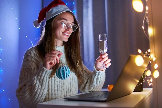 Молодая счастливая улыбающаяся радостная женщина в шляпе санта-клауса пьет шампанское