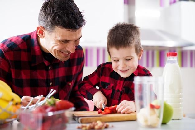 Молодой счастливый усмехаясь ребенок мужского пола думается как использовать ножи пока режущ клубники с его отцом на счетчике кухни.