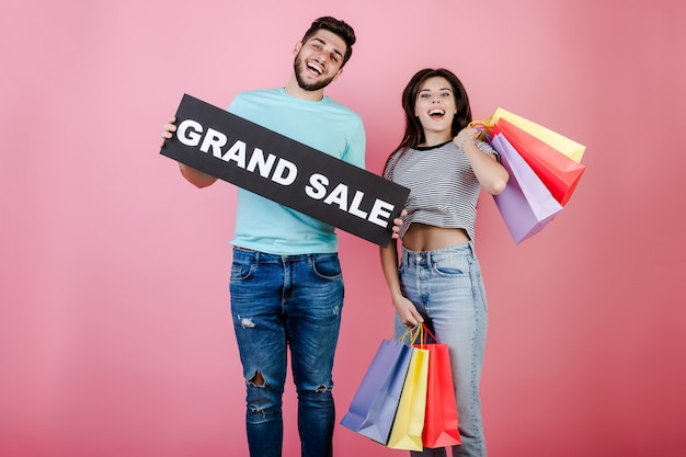 Young happy smiling man and woman jumping with grand sale sign and colorful shopping bags