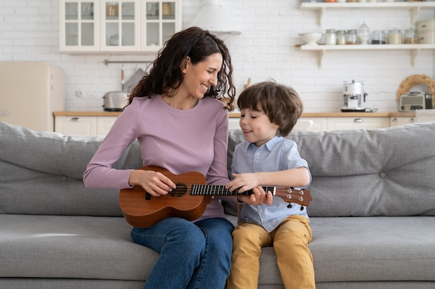 Young happy smiling mother and little son sit together on couch in living room play ukulele guitar