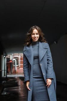 灰色のコートとタートルネックの若い幸せな笑顔のかわいい女の子が屋外でポーズします。魅力的な女性のストリートスタイルのポートレート写真撮影、美しいエレガントなモデルの都会的な写真撮影