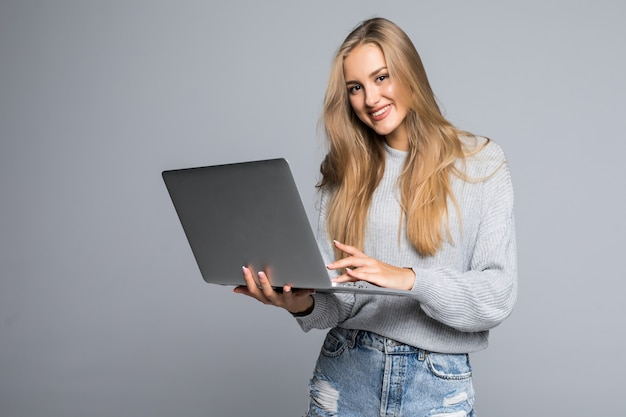 Young happy smiling woman in casual clothes holding laptop and sending email to her best friend isolated on gray background