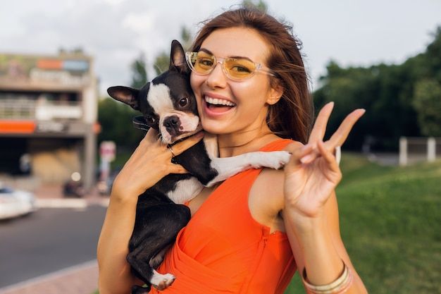 公園でボストンテリア犬を保持している若い幸せな笑顔の女性、夏の晴れた日、陽気な気分、ペットと遊ぶ、長い髪を振る、楽しんで、夏のファッショントレンド