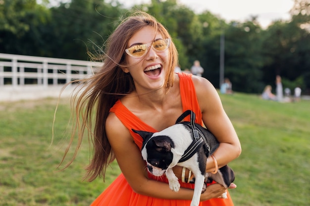 Young happy smiling woman holding boston terrrier dog in park, summer sunny day, cheerful mood, playing with pet, waving long hair, having fun, summer fashion trend