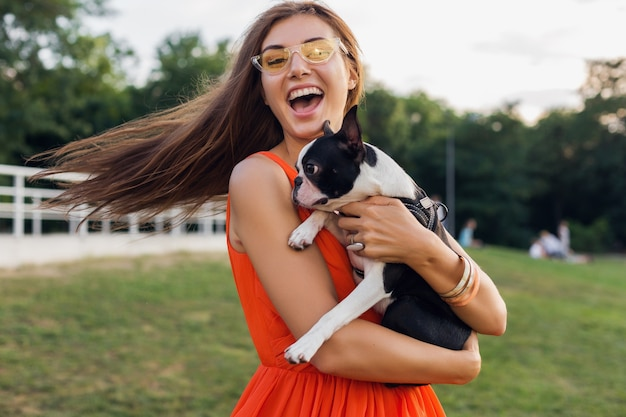 Young happy smiling woman holding boston terrrier dog in park, summer sunny day, cheerful mood, playing with pet, waving long hair, having fun, wearing sunglasses, laughing