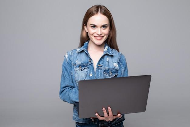 Молодая счастливая усмехаясь женщина в вскользь одеждах держа компьтер-книжку и посылая электронную почту к ее лучшему другу изолированному на серой стене