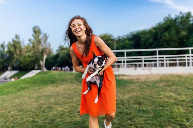 公園、夏のスタイル、陽気な気分で犬と遊ぶのを楽しんでオレンジ色のドレスで若い幸せな笑顔の女性