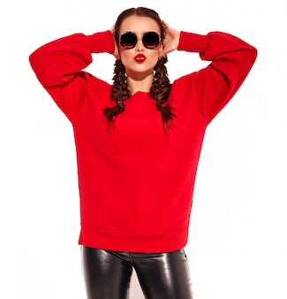 Young happy smiling woman model with bright makeup and colorful lips with two pigtails and sunglasses in summer red clothes isolated. giving air kiss