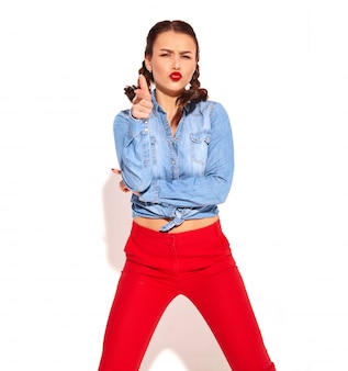 Young happy smiling woman model with bright makeup and red lips with two pigtails in summer blue jeans clothes isolated. imitating gun by her hand and shooting
