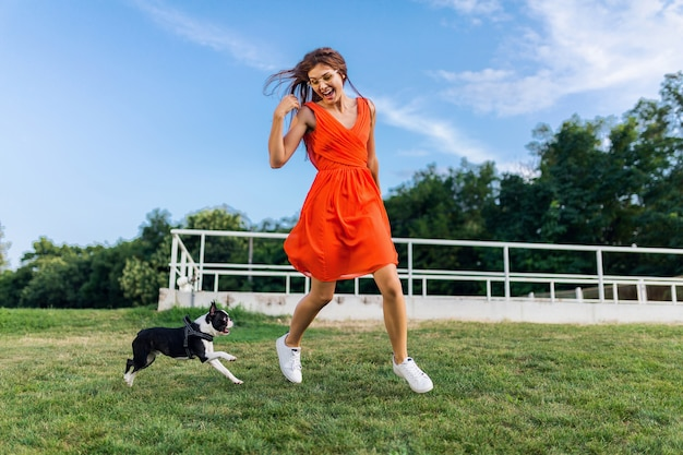 Young happy smiling woman in orange dress having fun playing running with dog in park, summer style, cheerful mood