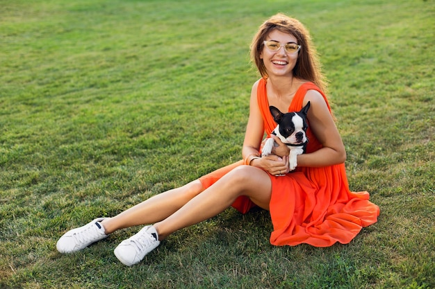 Giovane donna sorridente felice in vestito arancione divertendosi a giocare con il cane nel parco, stile estivo, umore allegro