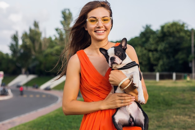 Young happy smiling woman in orange dress having fun playing with dog in park, summer style, cheerful mood