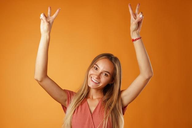 勝利のサインを示す若い幸せな笑顔の女性