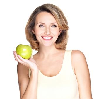 Молодая счастливая улыбающаяся женщина с зеленым яблоком, изолированным на белом.