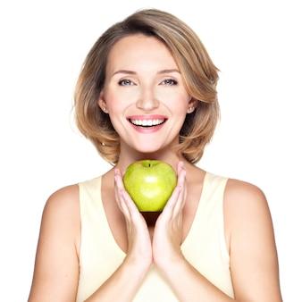 Молодая счастливая улыбающаяся женщина с зеленым яблоком - изолирована на белом.