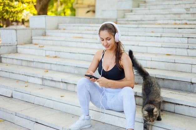 Молодая счастливая спортивная женщина в спортивной одежде использует смартфон и слушает музыку в наушниках, сидя на лестнице в яркий солнечный день