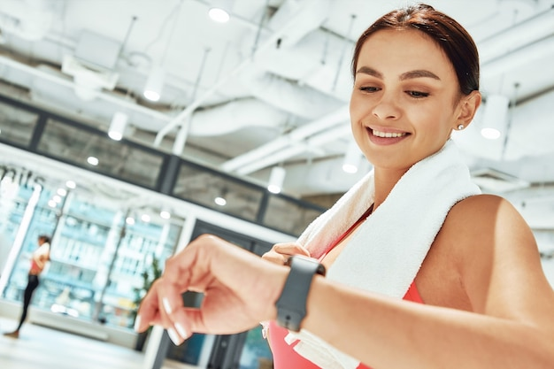 Young happy sportive woman with white towel on shoulders looking at smartwatch while exercising in