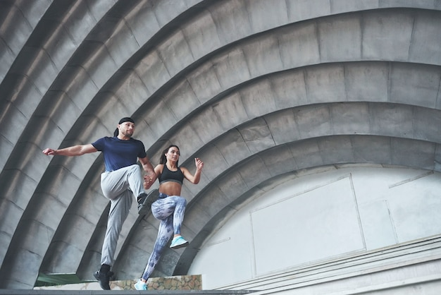 Young happy sports couple in the city street, performing parkour.