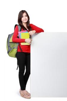 空白のボードで本を運ぶ若い幸せな学生