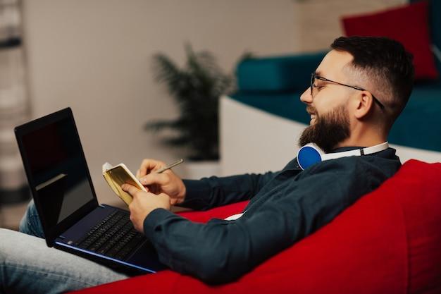 Молодой счастливый студент учится на современном ноутбуке онлайн дома. он делает записи в твоей записной книжке.